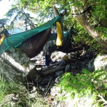 camping hammock setup over rocks