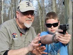 Bob teaching his son to shoot